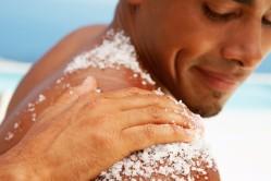 Hand Rubbing Bath Salt on Man's Shoulder